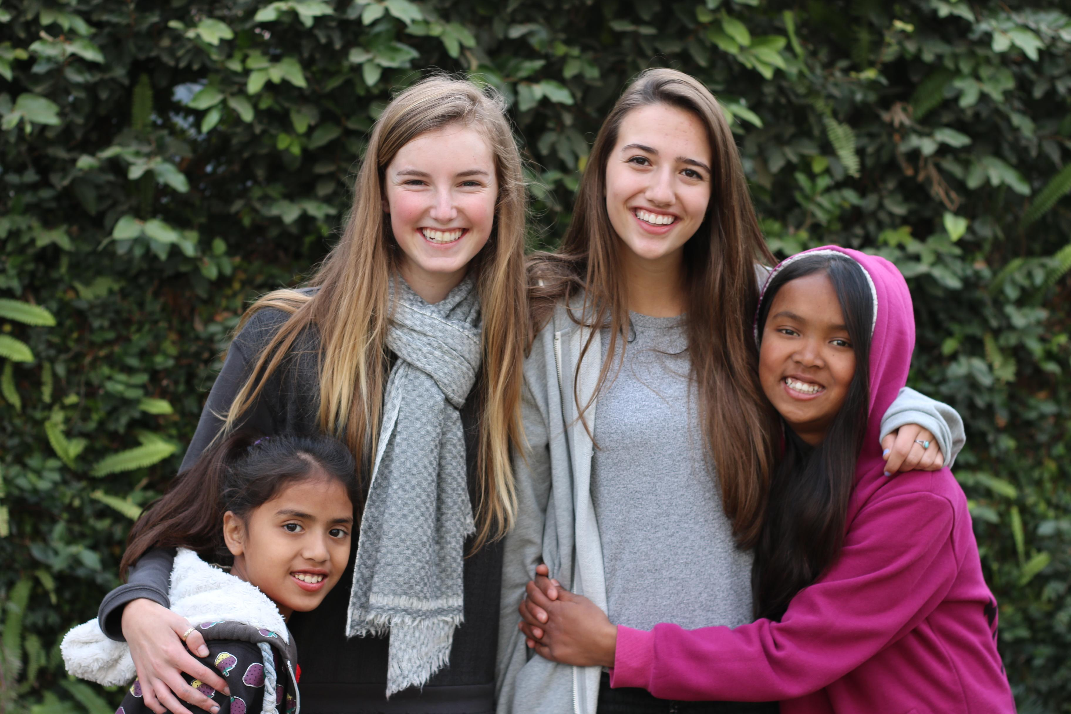 Teenage volunteers doing work with children in Nepal, take a photo with their students.